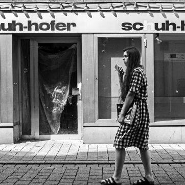 Junge Frau trägt ein kariertes Kleid und spricht mit ihrem Telefon