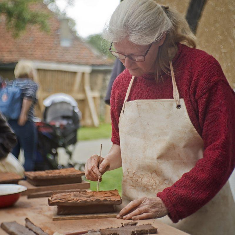 Keramikerin fertigt Kacheln